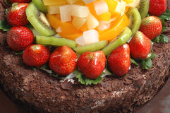 Fruits chocolate cake. It is a part view of chocolate cake, with lots of fruits, such as strawberries, Kiwi Royalty Free Stock Image
