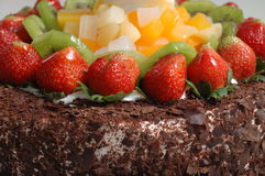 Fruits chocolate cake. It is a part view of chocolate cake, with lots of fruits, such as strawberries, Kiwi Royalty Free Stock Photography