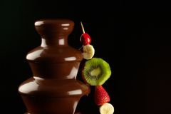 Fruits in chocolate fountain Royalty Free Stock Photo