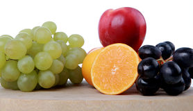 Fruits on chopping board 2. Sliced oranges, grapes, red grapes, apple on wood chopping board Royalty Free Stock Photography
