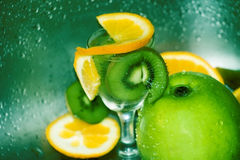 Fruits cocktail and water drops. Slices of oranges and kiwi and an apple, in fresh water Stock Photo