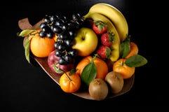 Fruits composition. With orange, grape fruit, apple, strawberry, banana and kiwi on black background Stock Image
