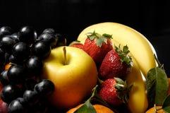Fruits composition. With orange, grape fruit, apple, strawberry, banana and kiwi on black background Royalty Free Stock Photos