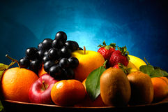 Fruits composition. With orange, grape fruit, apple, strawberry, banana and kiwi on blue background royalty free stock images