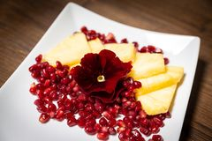 A fruits composition. Consisting of: pineapple, blackberry, pomegranate and an edible flower as decoration Royalty Free Stock Images