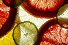 Fruits coupés en tranches colorés mélangés orange, chaux, pamplemousse, citron le fond de retour s'est allumé images stock