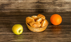 Fruits and croissants. On a wooden background Royalty Free Stock Photos