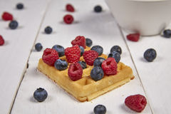 Fruits in a cup. Different berries on a waffle and in a bowl on a white wooden table Royalty Free Stock Photography