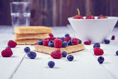 Fruits in a cup. Different berries on a waffle and in a bowl on a white wooden table Stock Photos
