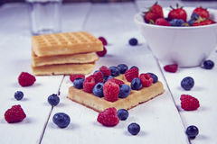 Fruits in a cup. Different berries on a waffle and in a bowl on a white wooden table Royalty Free Stock Images