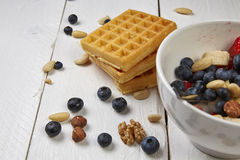 Fruits in a cup. Different berries on a waffle and in a bowl on a white wooden table Stock Photo