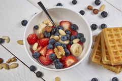 Fruits in a cup. Different berries on a waffle and in a bowl on a white wooden table Royalty Free Stock Photos