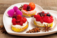 Fruits cupcakes  over heart plate Stock Image