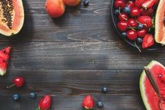 Fruits d'été Baies, pastèque et papaye juteuses fraîches sur la table en bois noire, vue supérieure photo libre de droits