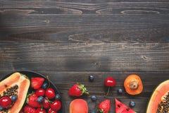 Fruits d'été Baies, pastèque et papaye juteuses fraîches sur la table en bois noire, vue supérieure photos stock
