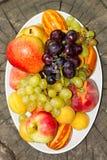 Fruits d'un plat sur un grand vieux tronçon d'arbre Image stock
