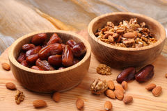Fruits dates and nuts in wooden bowl  on  table Royalty Free Stock Photos