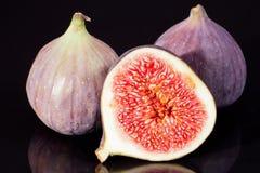 Fruits des figues fraîches d'isolement sur le fond noir Photo libre de droits