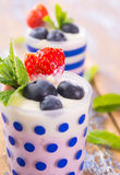 Fruits dessert. Strawberry and blueberry with yogurt and mint Stock Photo