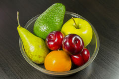 Fruits in dish on table. Diet, vegetable food, healthy eating and objects concept - close up of ripe fruits and vegetables in dish on table Royalty Free Stock Photo