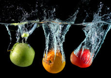 Fruits droping in to the clear water Stock Photos