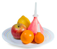 Fruits and enema. Two enemas, apple, lemon and orange on a plate isolated on white Stock Photography