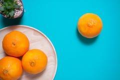 Fruits et jus oranges frais sur la table bleue de fond Photos libres de droits