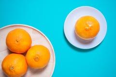 Fruits et jus oranges frais sur la table bleue de fond Photographie stock