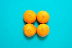 Fruits et jus oranges frais sur la table bleue de fond Images stock