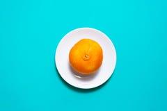 Fruits et jus oranges frais sur la table bleue de fond Image libre de droits