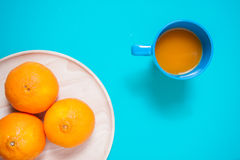 Fruits et jus oranges frais sur la table bleue de fond Image stock
