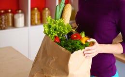 Fruits et légumes assortis dans le sac d'épicerie brun tenant une jeune fille image stock
