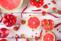 Fruits et légumes rouges sur un blanc sur un fond en bois Image libre de droits