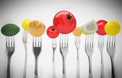 Fruits et légumes sur les fourchettes Nourriture saine Photos stock