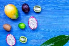 Fruits exotiques Dragonfruit, mangoustan, mangue, kiwi et chaux sur le copyspace en bois bleu de vue supérieure de fond Photographie stock