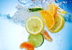 Fruits are falling under water with a splash