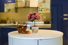 Fruits and flowers in blue interior kitchen Royalty Free Stock Photo