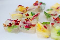 Fruits and flowers in ice cubes. Ice cubes with rose petals, mint and fruits Stock Photos