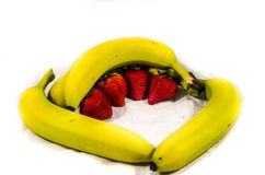 Four yellow and green banana`s and four strawberry`s. Fruits of four different banana cultivars Royalty Free Stock Photos
