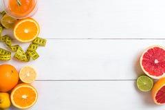 Fruits frais avec le ruban métrique au-dessus du fond en bois blanc Vue supérieure Image libre de droits