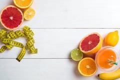 Fruits frais avec le ruban métrique au-dessus du fond en bois blanc Vue supérieure Image stock