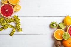 Fruits frais avec le ruban métrique au-dessus du fond en bois blanc Vue supérieure Photo libre de droits