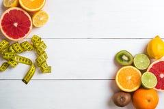 Fruits frais avec le ruban métrique au-dessus du fond en bois blanc Vue supérieure Photographie stock