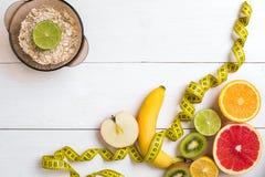 Fruits frais avec le ruban métrique au-dessus du fond en bois blanc Vue supérieure Photographie stock libre de droits