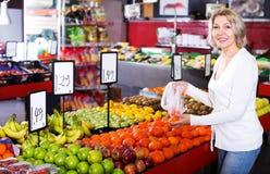 Fruits frais de achat de retraité féminin Photographie stock libre de droits