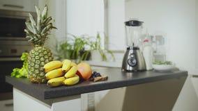 Fruits frais et mélangeur sur la table Banane, pomme, orange, ananas et raisins banque de vidéos