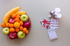Fruits frais et pilules colorés Concept sain de style de vie Photographie stock