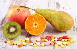 Fruits frais et pilules médicales colorées, choix entre la nutrition saine et les suppléments médicaux Photo libre de droits