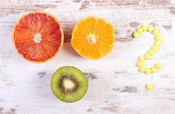Fruits frais et point d'interrogation fait de pilules médicales, choix entre la nutrition saine et les suppléments médicaux Photos stock