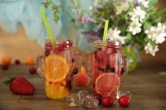 Fruits frais et smoothies sains de baies dans des bouteilles en verre avec des pailles sur une table en bois rustique d?cor?e des images stock